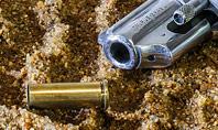Revolver on Sand with Scattered Cartridges Presentation Presentation Template